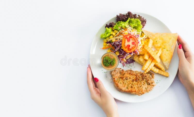 Bifes grelhados, batatas cozidas e vegetais na placa branca sobre imagens de stock