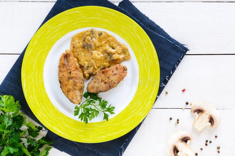 Bifes Roasted da carpa com molho de cogumelo em uma placa em um fundo de madeira branco imagem de stock royalty free