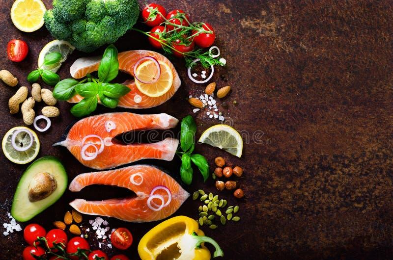 Bifes salmon crus, ervas aromáticas, cebola, limão, sal e legumes frescos para cozinhar no fundo de madeira Copyspace fotos de stock royalty free