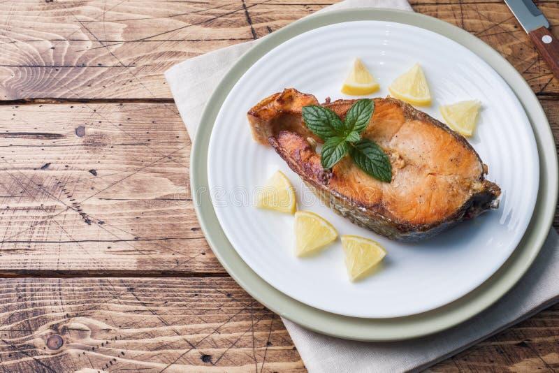 Biff bakade fisklaxen på en platta med citronen table trä arkivfoto