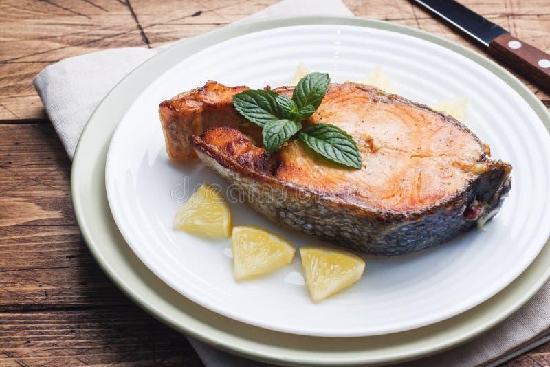 Biff bakade fisklaxen p? en platta med citronen table tr? arkivbilder