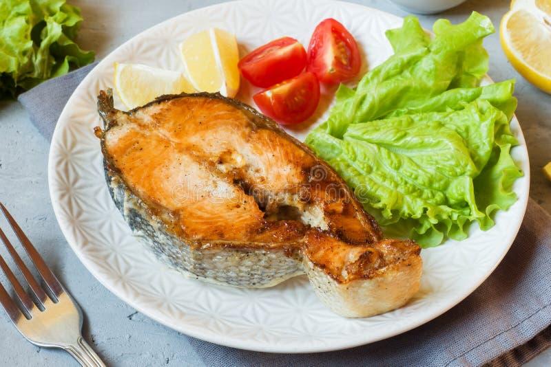 Biff bakade laxfisken p? en platta med nya gr?nsaker royaltyfri bild