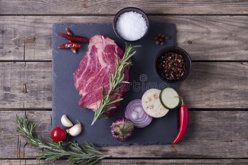 Biff för rått kött från marmornötkött med grönsaker på stenplattan Top beskådar arkivbilder