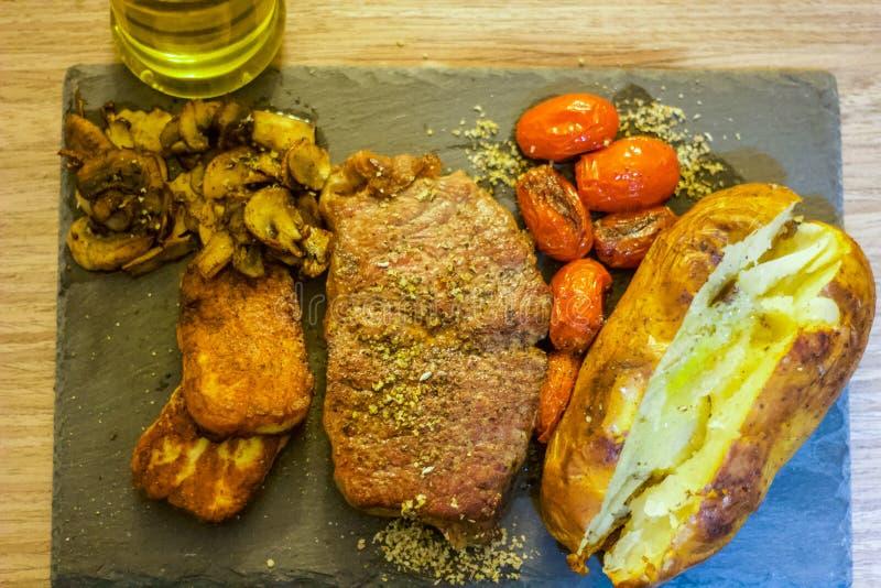 Biff, Halloumi och Baked potatis som lagas mat i organiska Olive Oil fotografering för bildbyråer