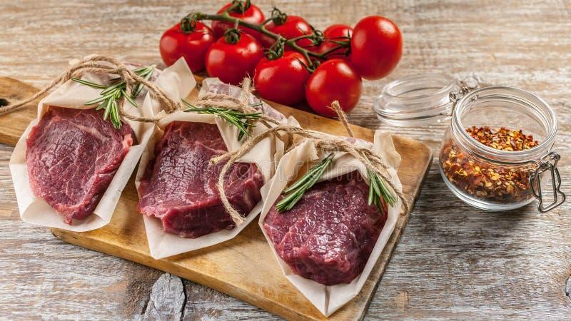 Biffar för rått kött, rosmarin, söta peppar och körsbärsröda tomater Nytt kött på en skärbräda, örter och grönsaker royaltyfri foto