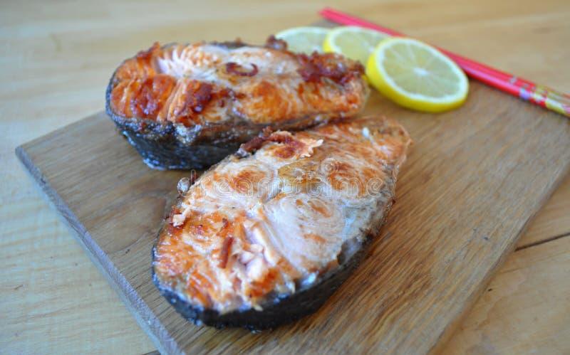 Biffar från röd fisk med citronen och sås royaltyfri foto