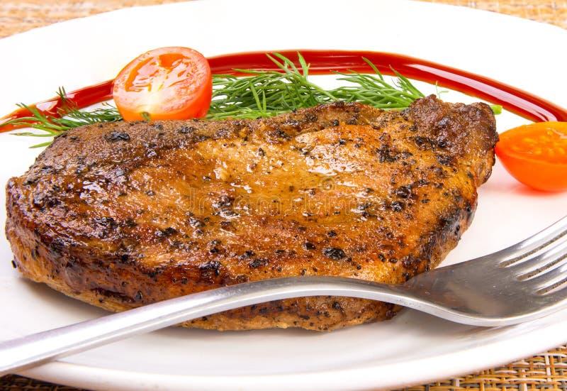 Biffkött med tomat- och grönsallatsalladbladet och gaffel i en vit platta royaltyfri foto