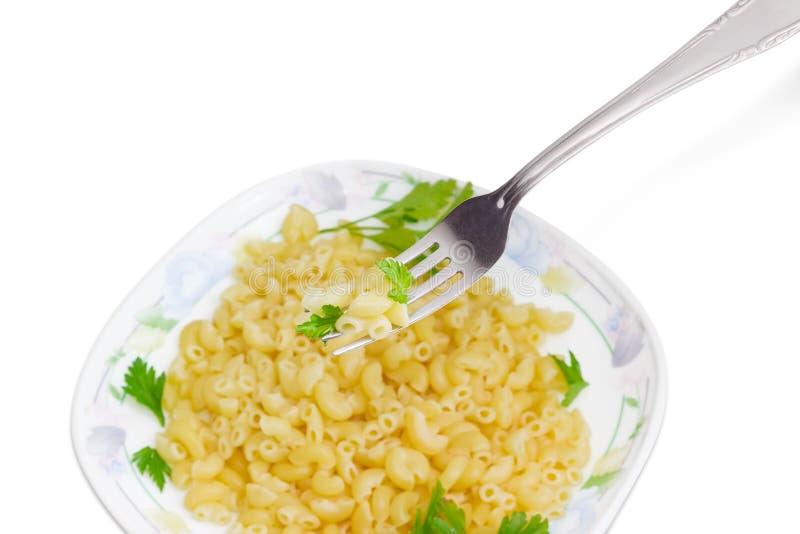 Biforchi con brevi maccheroni curvi cucinati sopra il piatto con pasta fotografia stock