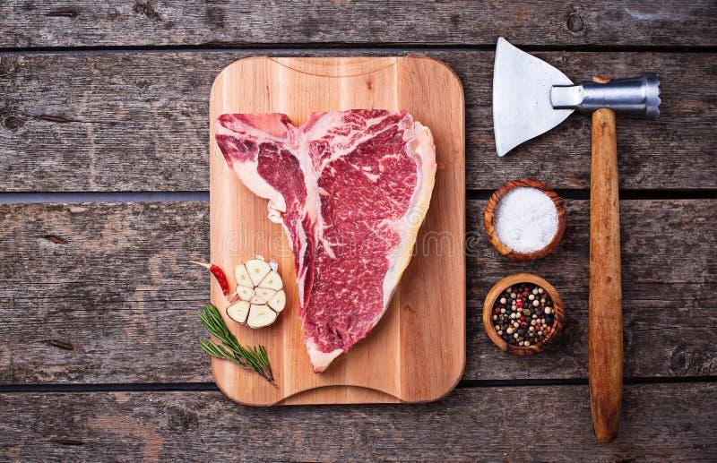 Bifteck à l'os cru avec la cognée photographie stock