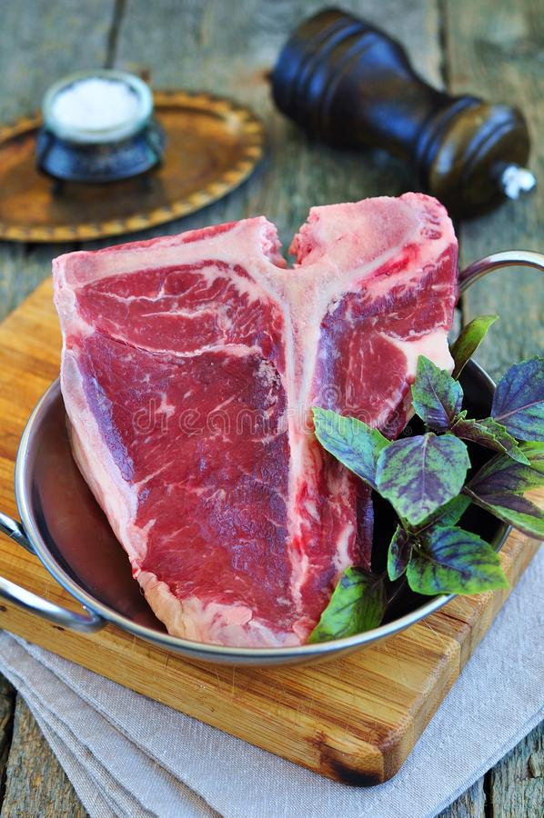 Bifteck à l'os de boeuf cru juteux sur la table en bois Foyer sélectif l'image est teintée photos libres de droits