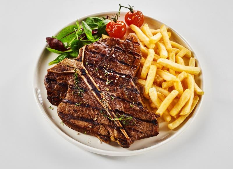 Bifteck ? l'os grill? avec des pommes frites photographie stock