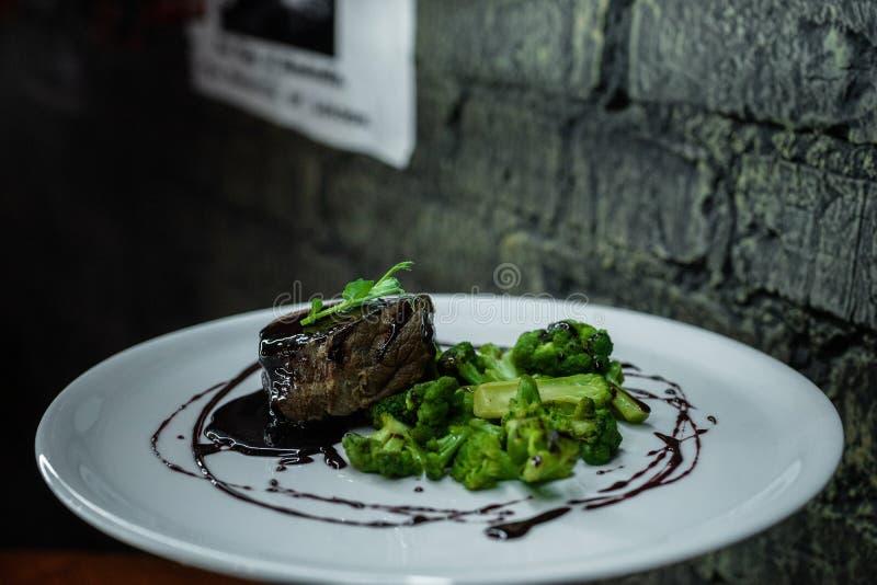 Bifteck appétissant de porc avec le brocoli cuit au four en sauce au vin rouge sur une table dans un restaurant de cru Déjeuner d image libre de droits