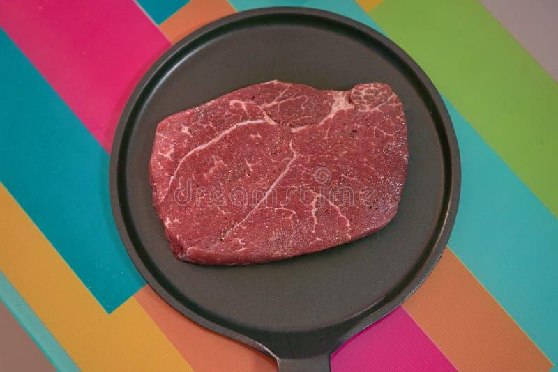 Bifteck aromatisé de viande crue pour le cuisinier sur non la casserole de bâton sur t coloré images stock