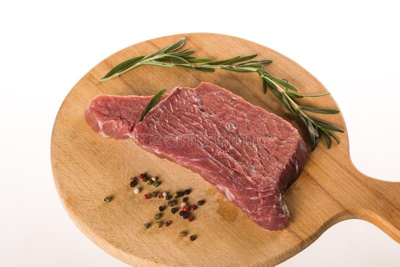 Bifteck avec les graines et le romarin de poivre sur le bureau en bois photo libre de droits
