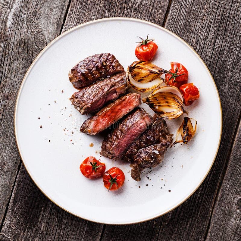Bifteck coupé en tranches Ribeye aux oignons et aux tomates photo stock