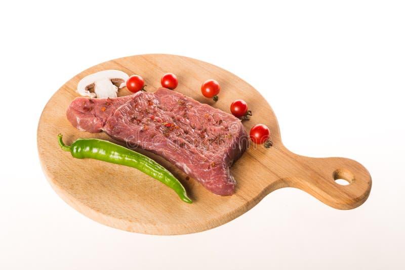 Bifteck cru avec des épices et des légumes de plat en bois image libre de droits