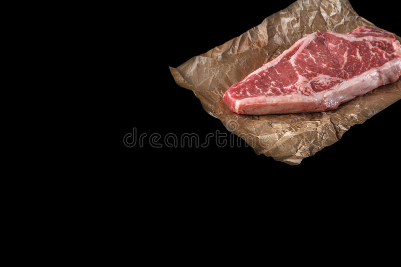 Bifteck cru de New York de striploine sur le fond noir photos stock