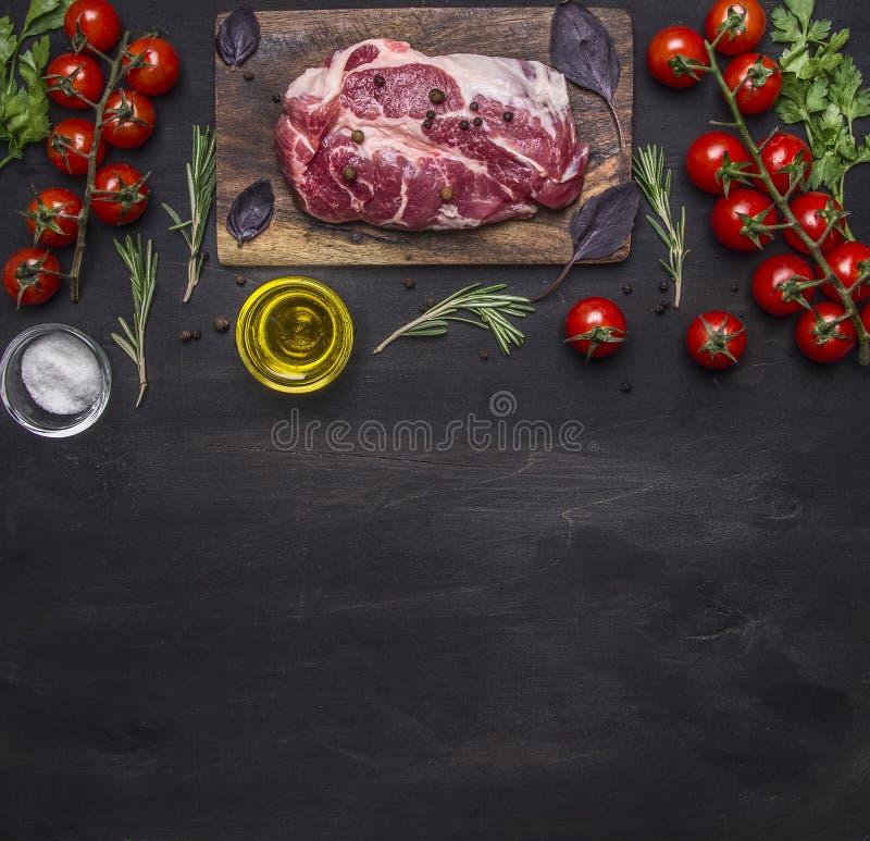 Bifteck cru de porc pour le gril, sur une planche à découper avec des légumes et des herbes, frontière de romarin, endroit pour l photos stock