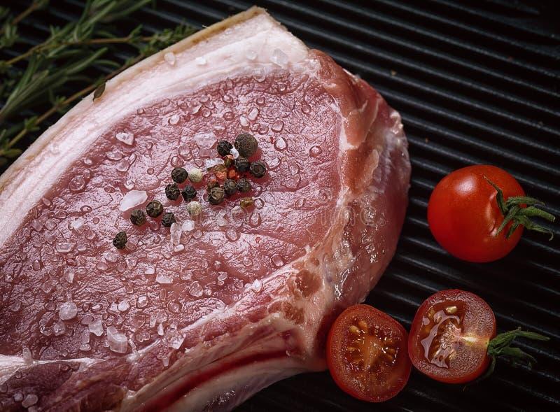 Bifteck cru de porc sur des nervures la casserole de gril image libre de droits
