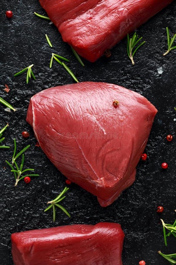 Bifteck cru de venaison avec le romarin et le poivre sur la table rustique noire photographie stock libre de droits