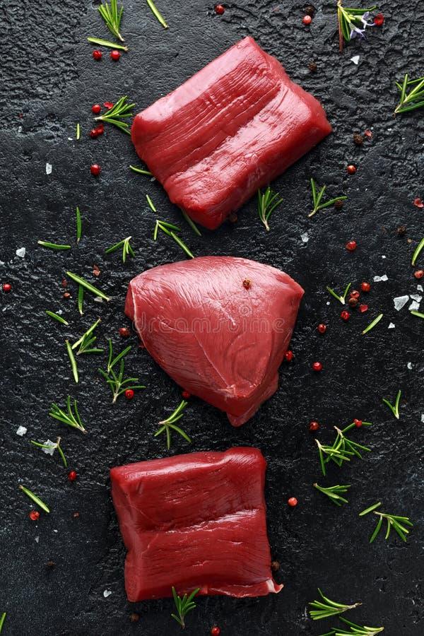 Bifteck cru de venaison avec le romarin et le poivre sur la table rustique noire image stock