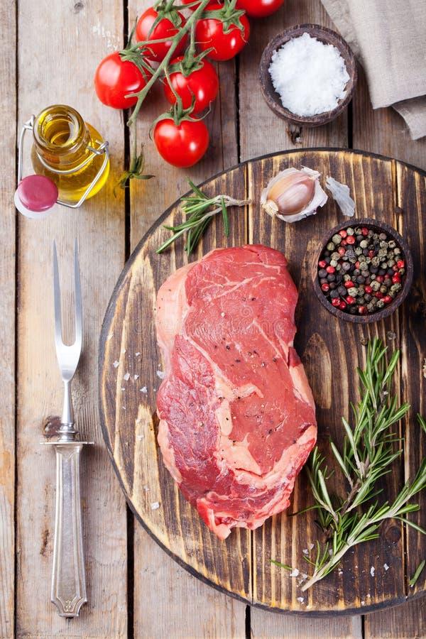 Bifteck cru de viande fraîche avec du sel et poivre, romarin et tomates sur la planche à découper sur la vue supérieure de fond e photos stock