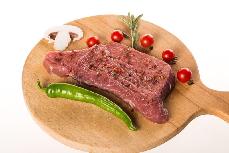 Bifteck cru de viande sur le bureau en bois avec le romarin, poivre, tomates images stock