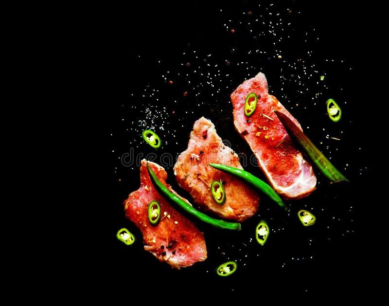 Bifteck cru et poivrons de piment verts sur un fond noir avec des épices image libre de droits