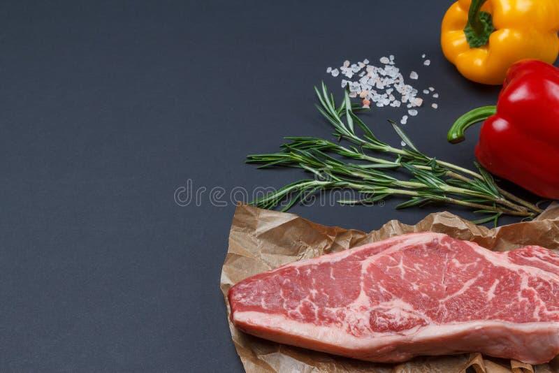 Bifteck cru frais de New York de striploin avec le romarin, le poivre et le p image stock