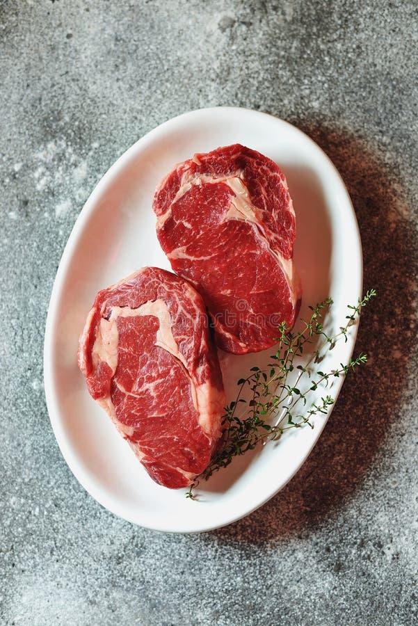 Bifteck cru juteux avec le thym sur un fond gris Nourriture saine organique Vue sup?rieure photos stock