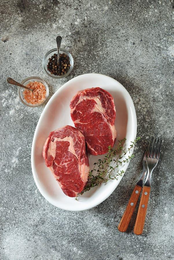 Bifteck cru juteux avec le thym sur un fond gris Nourriture saine organique Vue sup?rieure photo stock