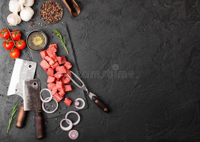 Bifteck découpé maigre cru de porc de boeuf de cocotte en terre avec la cognée de viande de cru et fourchette sur le fond en pier images libres de droits