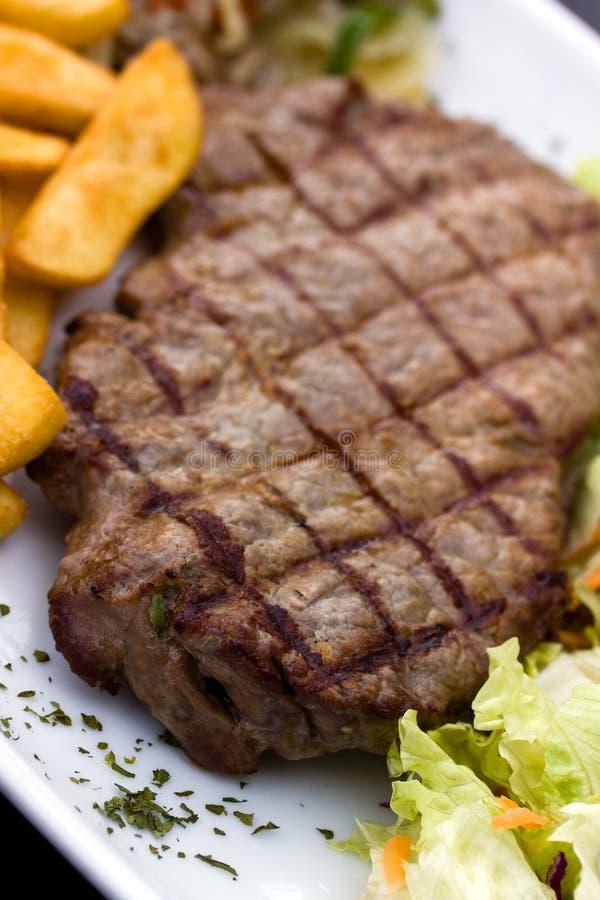 Bifteck d'aloyau avec des puces, champignons de couche, salade photos libres de droits