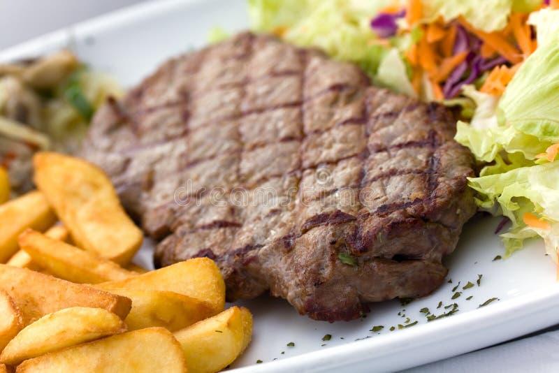 Bifteck d'aloyau avec des puces, champignons de couche, salade photo stock