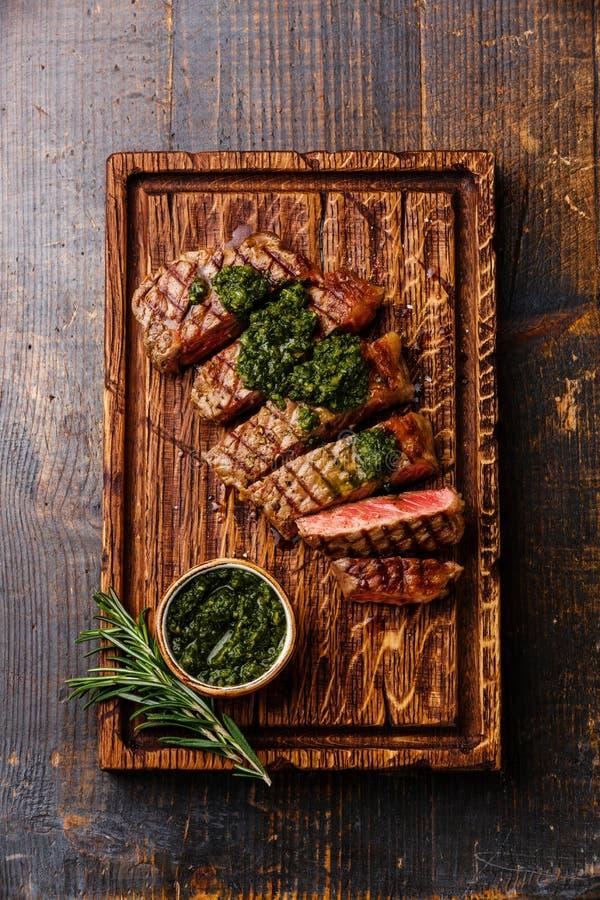 Bifteck d'aloyau coupé en tranches de boeuf avec de la sauce à chimichurri photos libres de droits