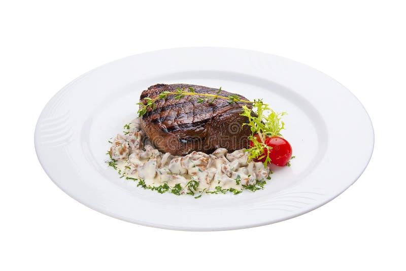 Bifteck de boeuf avec des champignons de forêt D'un plat blanc photos stock