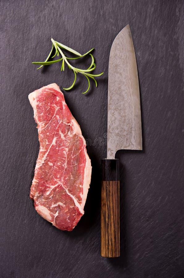 Bifteck de boeuf avec le couteau de Santoku photographie stock libre de droits