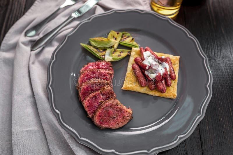 Bifteck de boeuf coupé en tranches avec les légumes grillés d'un plat photographie stock
