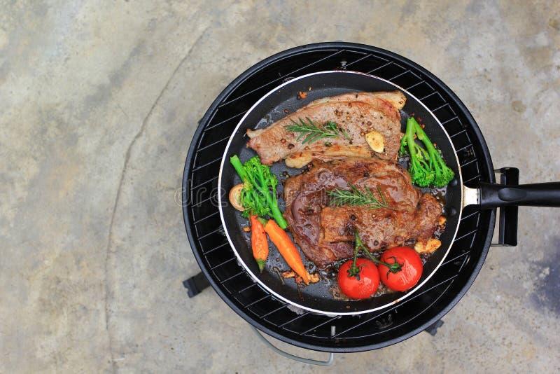 Bifteck de boeuf cru avec des légumes dans la poêle sur le fond de plancher de tuiles, la viande de nourriture ou le barbecue photographie stock libre de droits