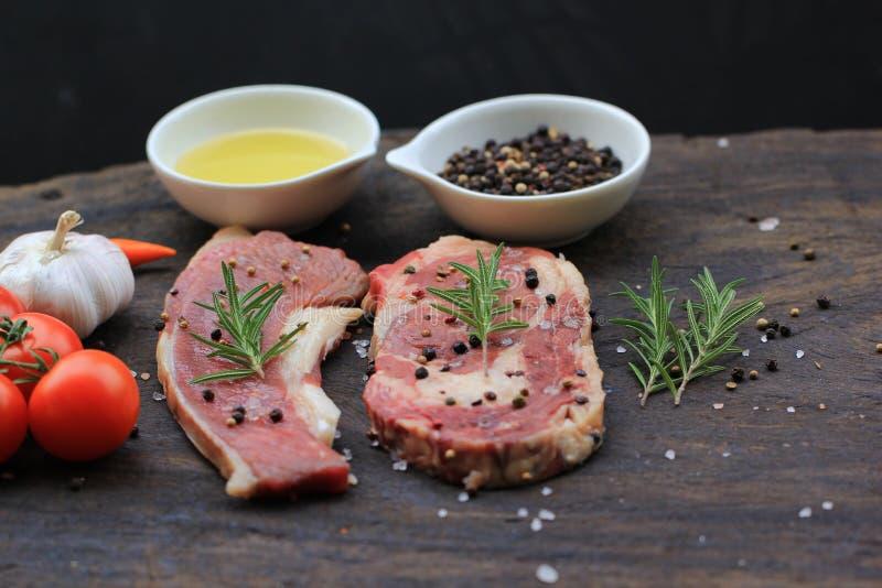 Bifteck de boeuf cru avec le romarin et les légumes sur le fond, la viande de nourriture ou le barbecue foncée en bois image stock