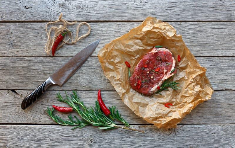 Bifteck de boeuf cru sur le fond en bois foncé de table, vue supérieure photo stock