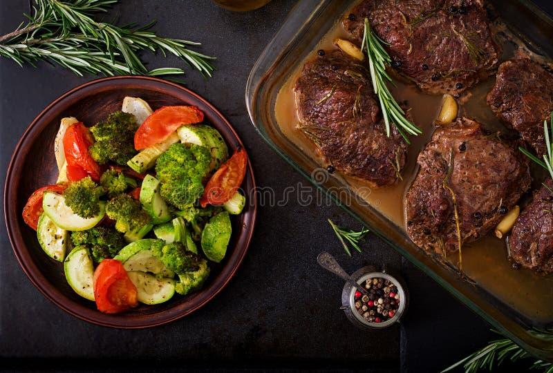 Bifteck de boeuf cuit au four avec l'ail et le romarin et les légumes images libres de droits