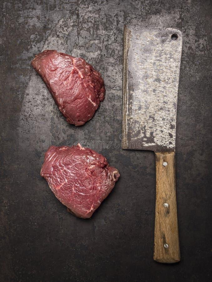 Bifteck de boeuf deux cru frais avec le fendoir de viande sur la vue supérieure de fond rustique foncé image libre de droits