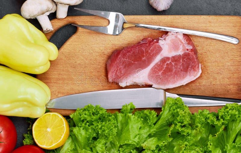 Bifteck de boeuf frais, cuillère en bois, couteau et assortiment des légumes frais, herbes aromatiques, épices et légumes pour fa photographie stock