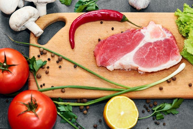 Bifteck de boeuf frais, cuill?re en bois, assortiment des l?gumes frais, herbes aromatiques, ?pices et l?gumes pour la cuisson image stock