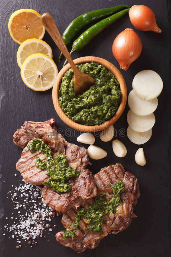 Bifteck de boeuf grillé avec de la sauce à chimichurri sur le panneau d'ardoise Vertic image stock