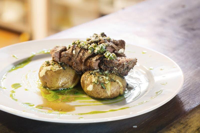 Bifteck de boeuf grillé avec de la sauce et la pomme de terre à ail photographie stock libre de droits
