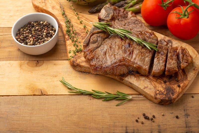 Bifteck de boeuf marbré sur un conseil avec le poivre de romarin, les épices, et les légumes frais, les tomates et l'asperge, art photographie stock libre de droits