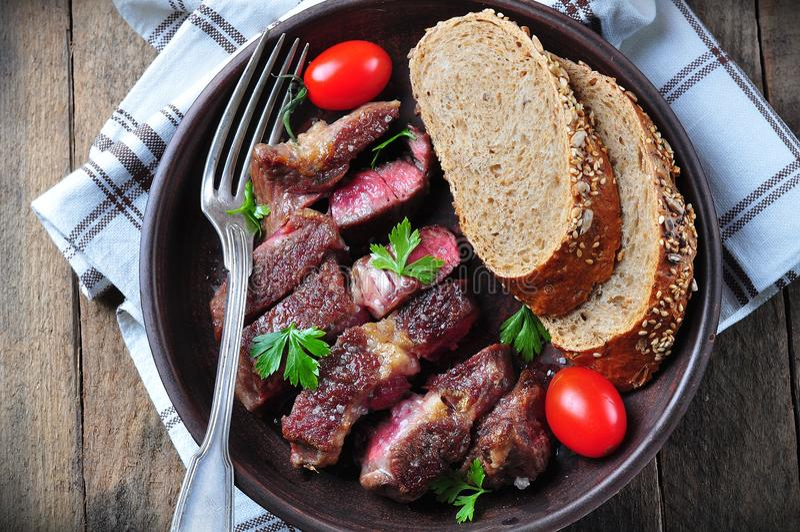 Bifteck de boeuf rare juteux délicieux avec le son de pain de seigle photo libre de droits
