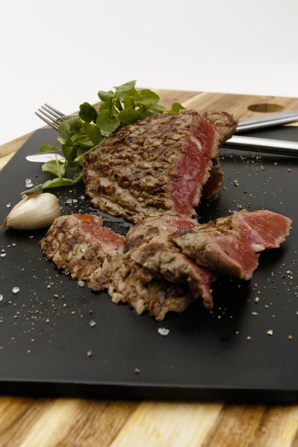 Bifteck de boeuf rare succulent et juteux, avec la garniture de cresson et d'ail image stock